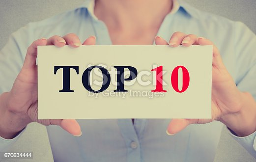 istock Closeup businesswoman hands holding white card sign with top 10 text message 670634444