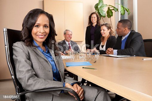 Businesswoman with team working in background.View More.