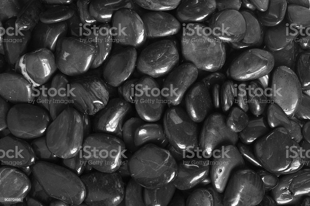 Closeup BW Smooth Polished Black Pebble Rocks Background stock photo