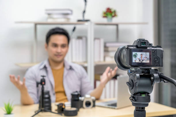 Closeup Camera taking video and live with laptop of Asian Vlogger man