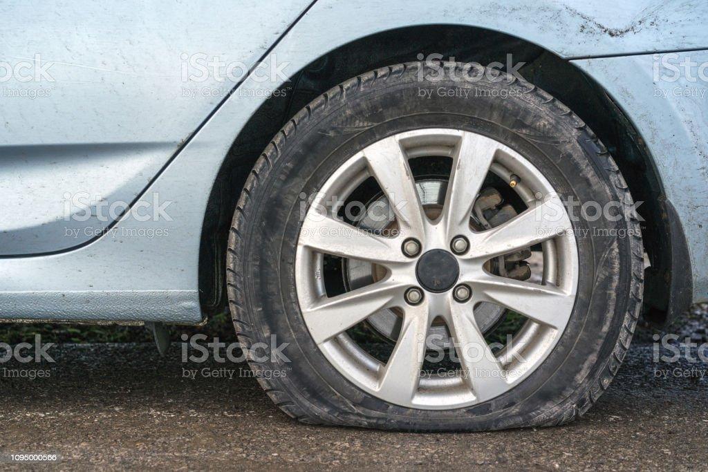 closeup car flat tire in rainy day on road stock photo