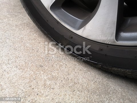 Close-up car tires have a tear on the sidewall. Flat tire on a car