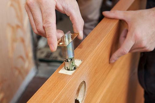 Close-up carpenter hands door lock installation.
