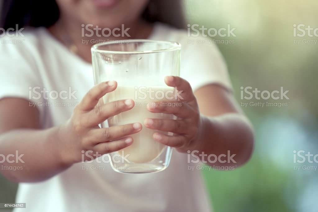 Closeup child hand holding a glass of milk stock photo