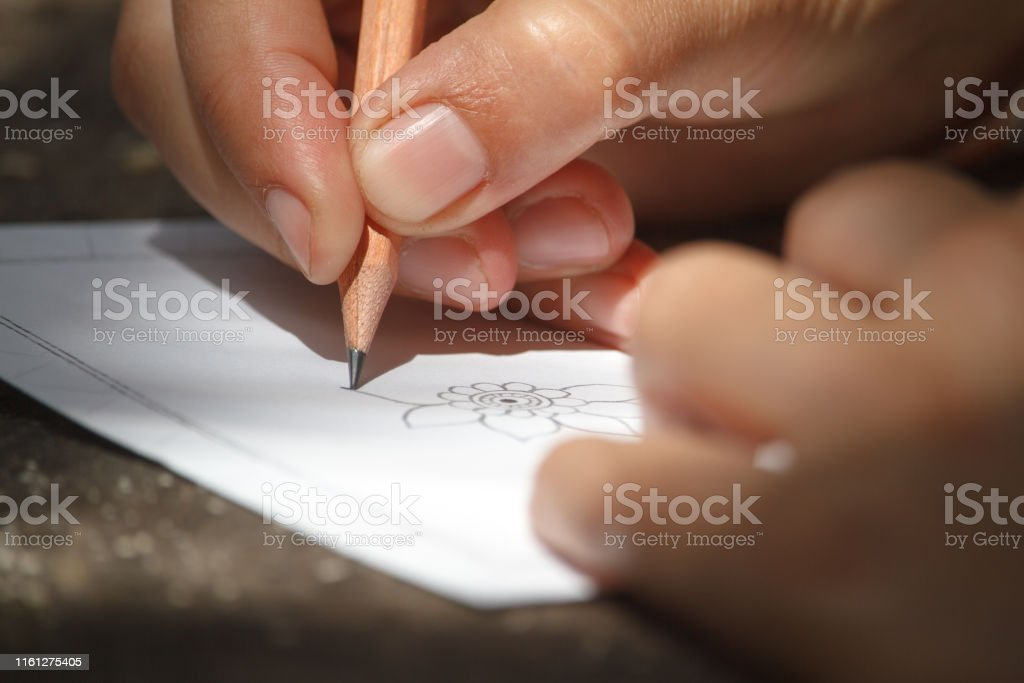 Closeup childs hand draws a flower with a pencil on a white sheet of...