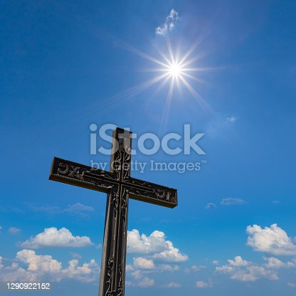 closeup christian cross uplift on the cloudy sky with sparkle sun background