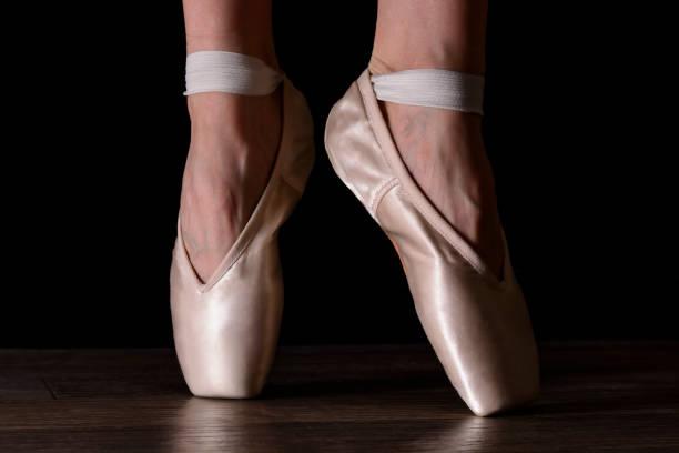 Close-up klassische Ballerina Beine Pointes auf schwarzem Hintergrund und grauen Holzboden. – Foto
