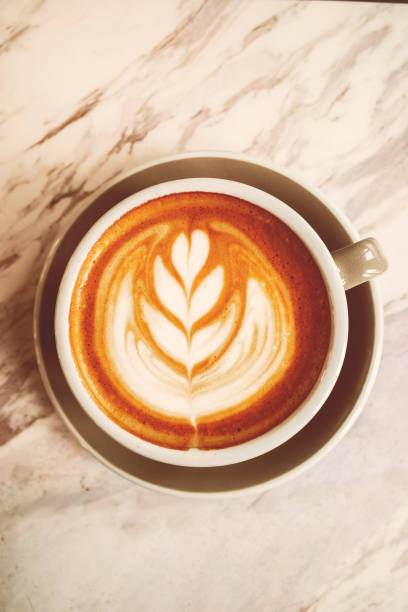 Closeup Coffee latte art leave from fresh milk foam on side of marble stock photo