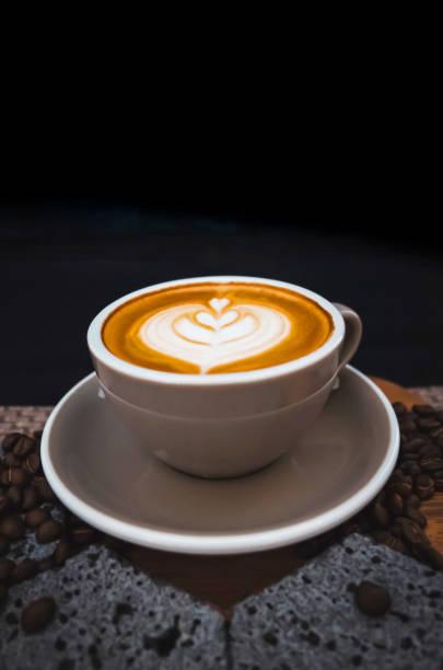 Closeup Coffee latte art leave from fresh milk foam on side of wood stock photo