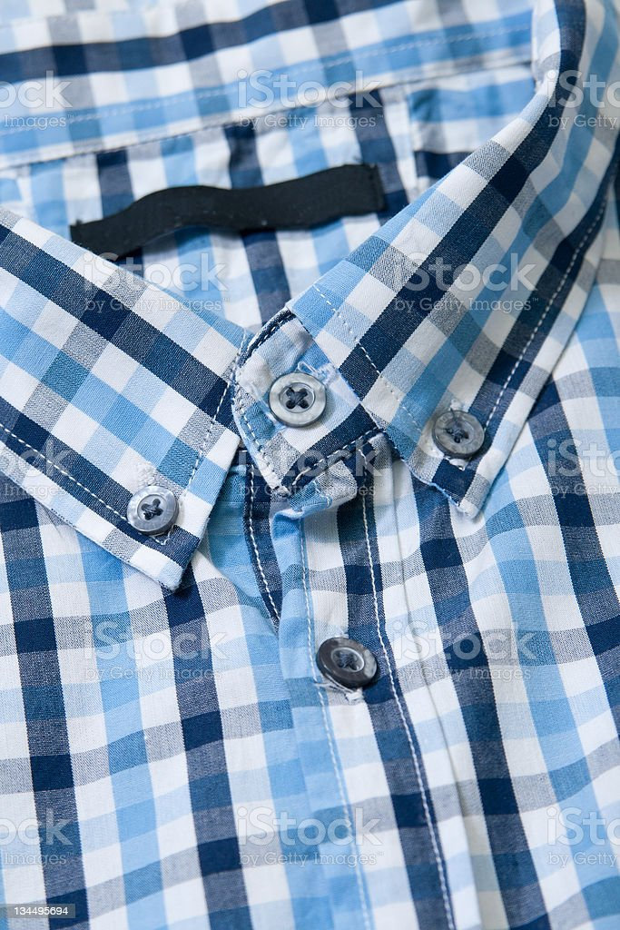 Close-up collar men's shirts in a cell, blue royalty-free stock photo