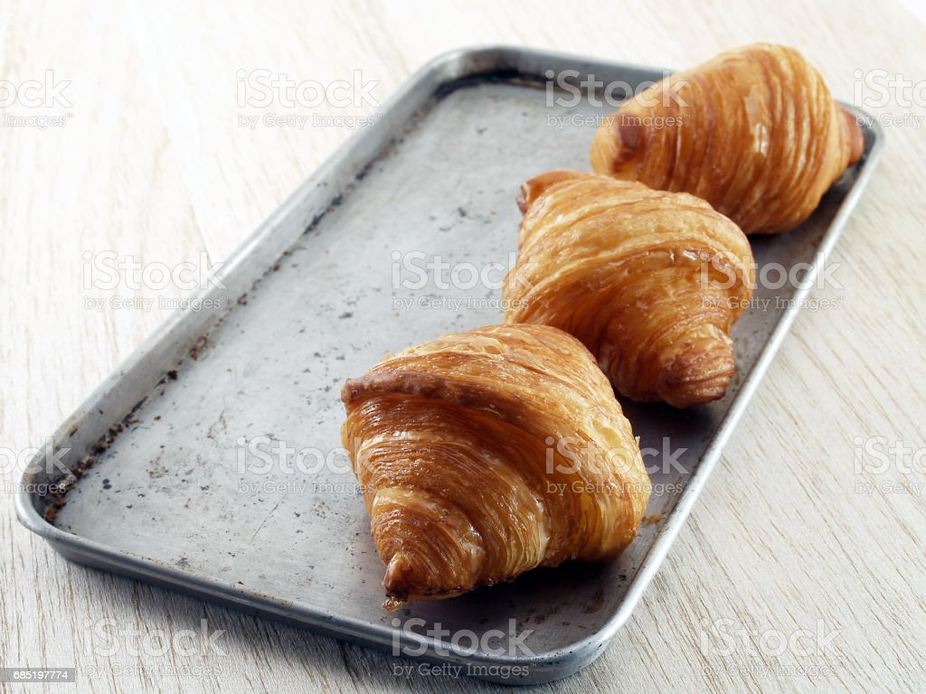 closeup croissant on oven tray and wooden table floor stock photo