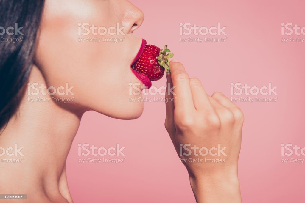 Close-up cropped half face profile side view portrait of lovely Close-up cropped half face profile side view portrait of lovely sweet feminine glamorous attractive wavy-haired lady eating biting licking tasting enjoying dessert red lips isolated on pink background Adult Stock Photo