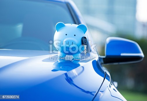 istock Closeup cropped image blue new car with piggy bank and key on hood, isolated outside corporate building 672030274