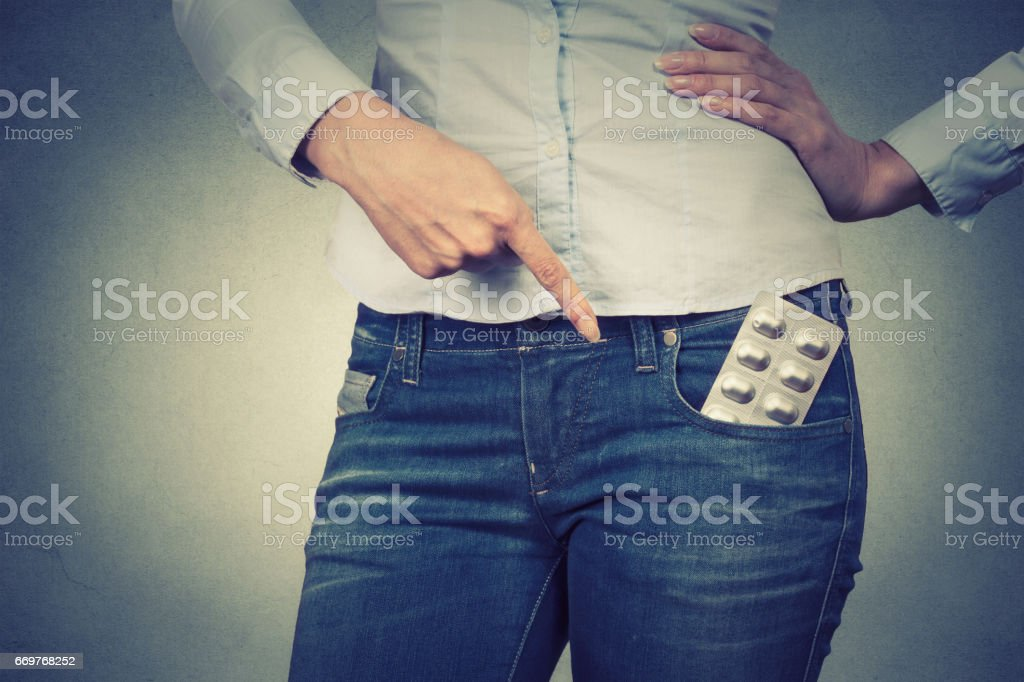 Closeup cropped image of a woman pointing with finger at pills in her pocket on gray background stock photo