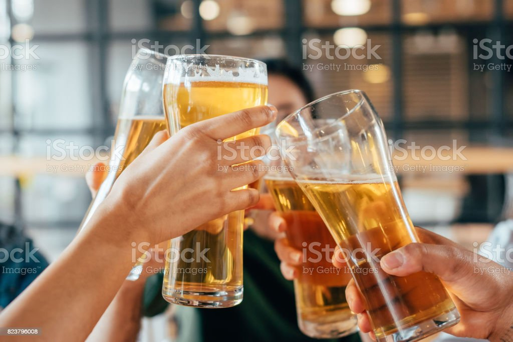 Close-up cropped image of friends clinking with beer in cafe stock photo