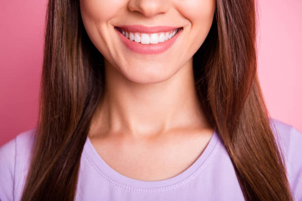Closeup cropped photo of beautiful woman with brunette hair smiling with white teeth isolated on pastel pink color background stock photo