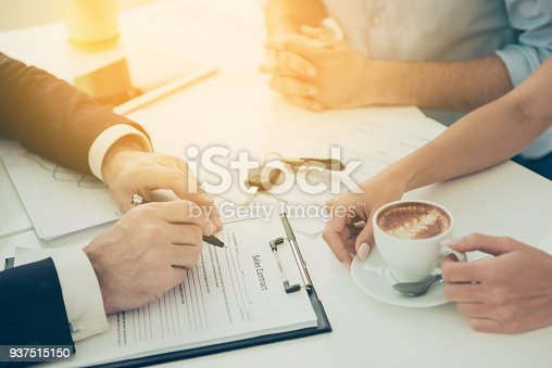 istock Closeup cropped photo of  broker and a family couple signing a contract in a cafe 937515150