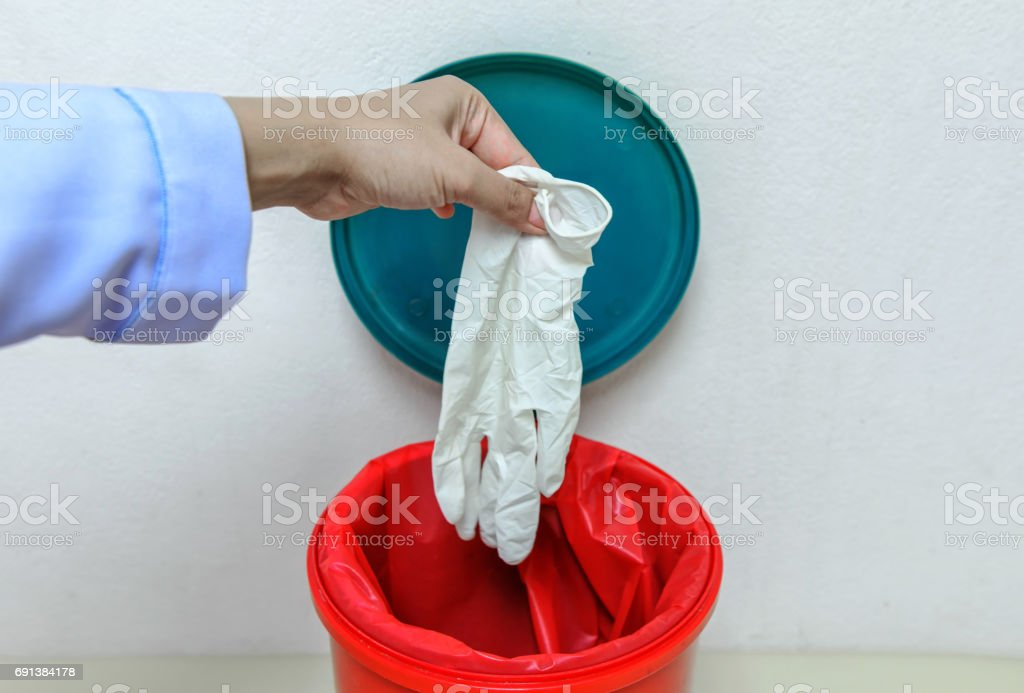 Closeup cropped portrait, healthcare professional throwing away blue disposable latex gloves in trash.lsolated lab background.infectious wastes in red bag in hospital. stock photo