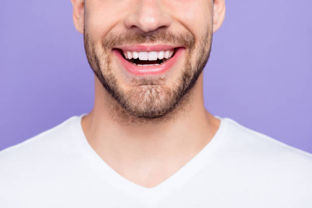 close-up cropped portrait of attractive, trendy, stylish, toothy man with wide beaming smile and healthy teeth, over pastel violet purple background - mouth imagens e fotografias de stock