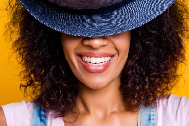 closeup recortada retrato de muchacha positiva alegre con dientes rectos blanco escondiendo la mitad de la cara con sombrero aislado en fondo amarillo - accesorio de cabeza fotografías e imágenes de stock