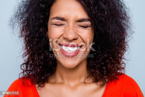 Closeup cropped portrait of funny comic woman with clenched white healthy teeth close eyes making a wish isolated on grey background. Toothcare tooth care treatment therapy concept