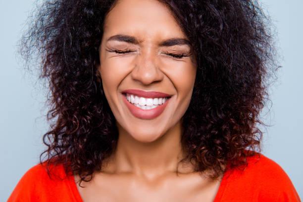 Closeup recadrée portrait d'une femme comique drôle avec le blanc des dents saines ferment yeux faire un vœu isolé sur fond gris. Concept de thérapie Toothcare dent soins traitement - Photo