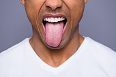 istock Close-up cropped portrait of his he handsome attractive well-groomed virile funky guy wearing white shirt showing tongue out isolated over gray violet purple pastel background 1129155744