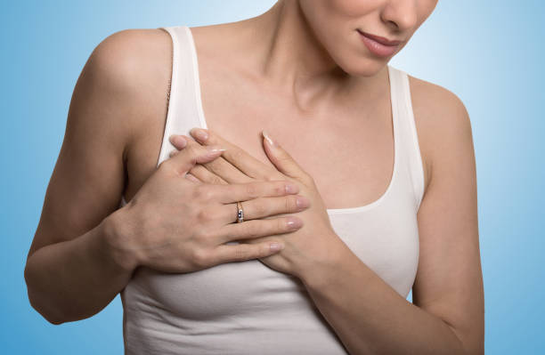 closeup cropped portrait young woman with breast pain touching chest colored isolated on blue background - seno foto e immagini stock