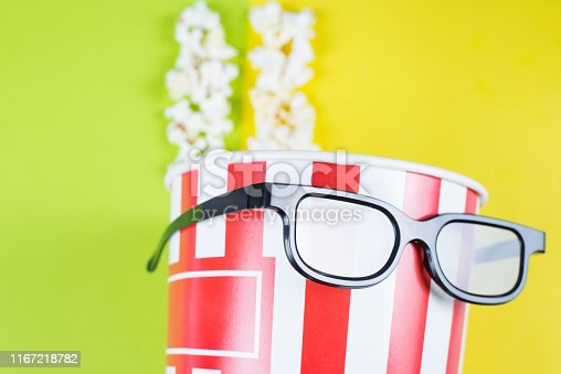 956942702 istock photo Closeup cropped view photo of paper box with tasty popcorn wearing black cool with reflection specs behaving like a human enjoying premiere isolated colorful background 1167218782