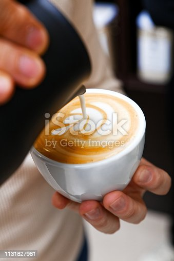 Closeup cup of cappuccino or latte in coffee-shop. Barista holding and pouring milk to make latte art. Shallow focus.
