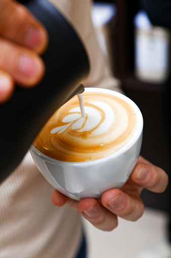 istock Closeup cup of cappuccino. Barista holding and pouring milk to make latte art 1131827981