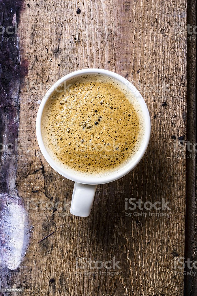 Closeup cup of espresso on old wooden table over grunge royalty-free stock photo