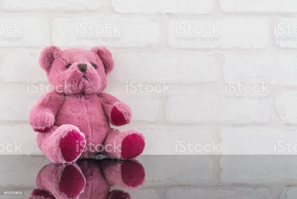 Closeup cute pink bear doll on black glass table and white brick wall textured background with copy space stock photo