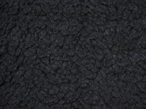 Close-up dark gray wool texture. Knitwear, background of oxford gray fluffy woolen. Fleece sheep