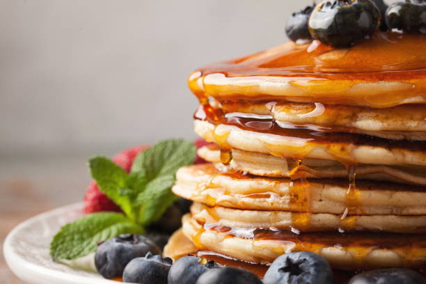 close-up delicious pancakes, with fresh blueberries, strawberries and maple syrup on a light background. sweet maple syrup flows from a stack of pancake - xarope imagens e fotografias de stock