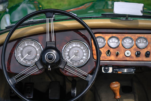 Close-up, detailed photo of the interior of a classic oldtimer luxury sports car. Close-up, detailed photo of the interior, dashboard, steering wheel and speedometer of a classic oldtimer luxury sports car. dashboard vehicle part stock pictures, royalty-free photos & images