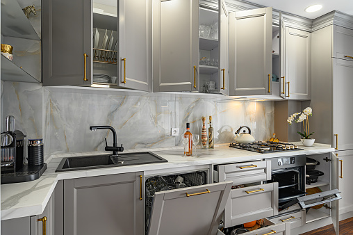 Closeup details of grey and white contemporary classic kitchen designed in modern style, all furniture doors and drawers are open