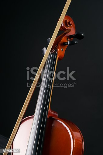 istock Close-up details of  Violin with violin bow  isolated on black background with copy space. 697997602