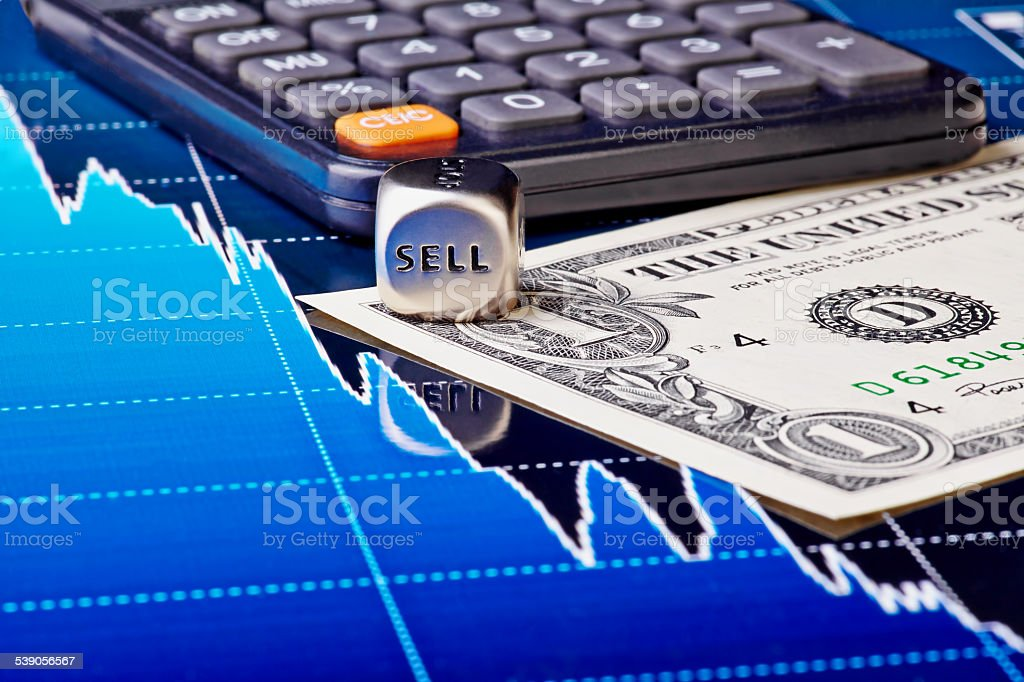 Close-up dices cube with the word SELL, one-dollar banknote stock photo