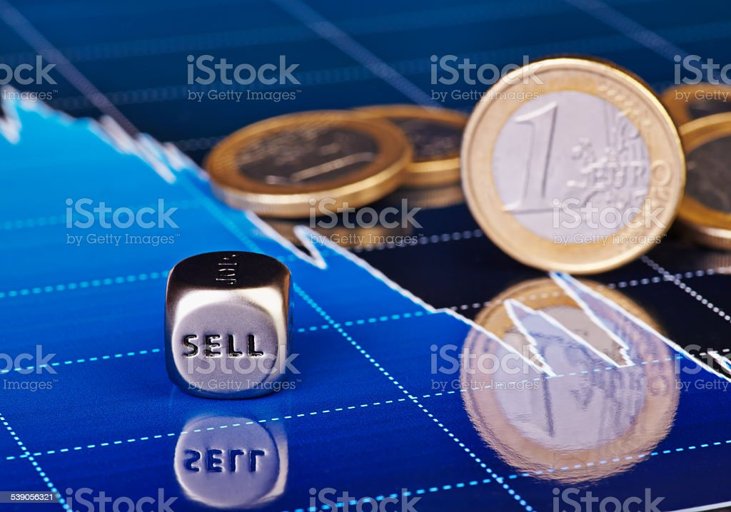 Close-up dices cube with the word SELL, one-euro coins stock photo