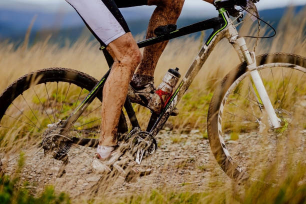 close-up dirty cyclist and mountain bike stock photo