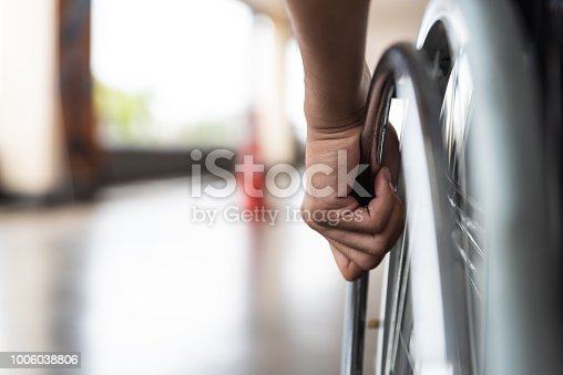 closeup disabled man hand on wheel of wheelchair