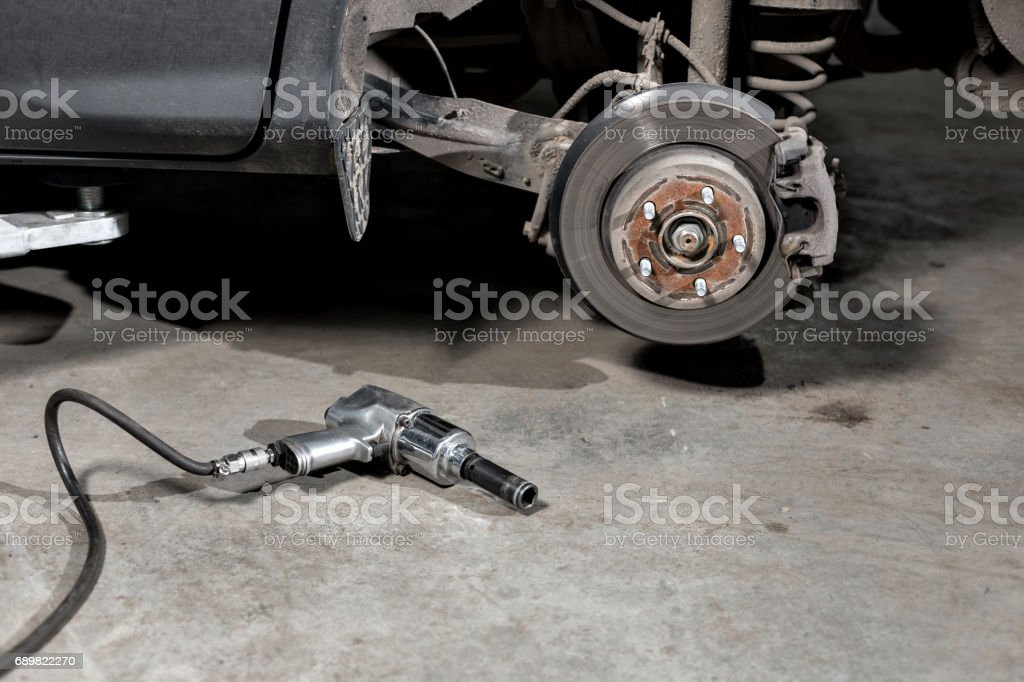 Closeup disc brake of the vehicle for repair. shot wheel, the tool for loosening the nuts. internal screw stock photo