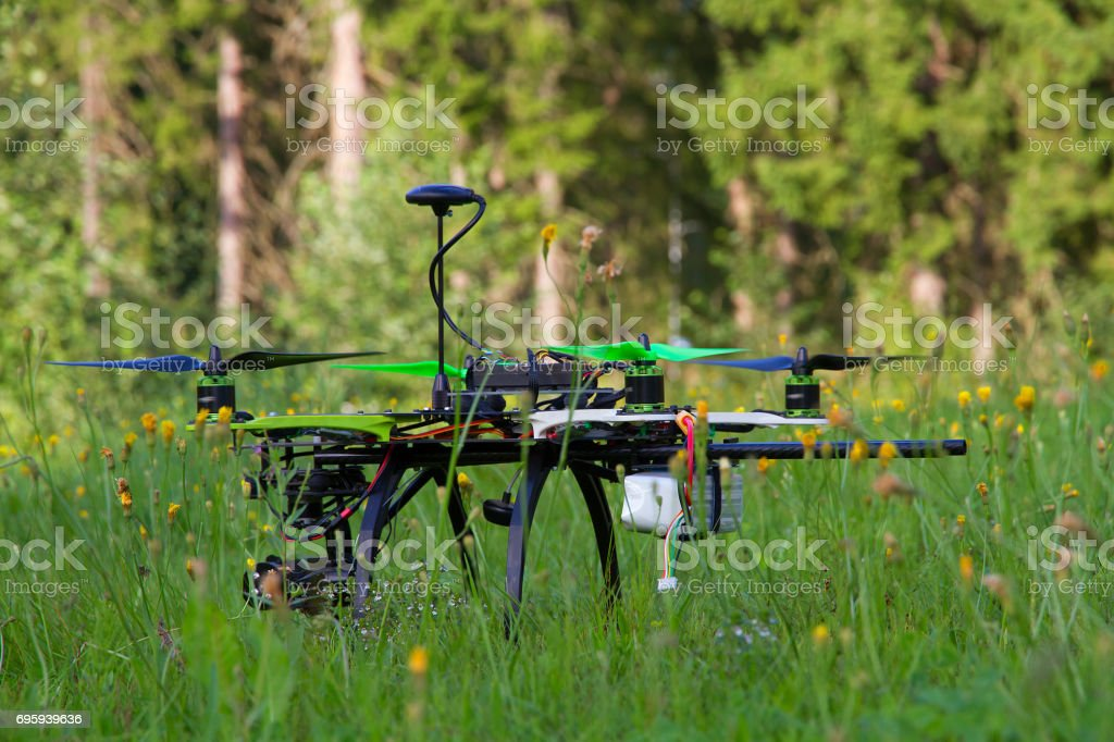 Close-up drone with green props and antenna in the green grass in a summer day. стоковое фото