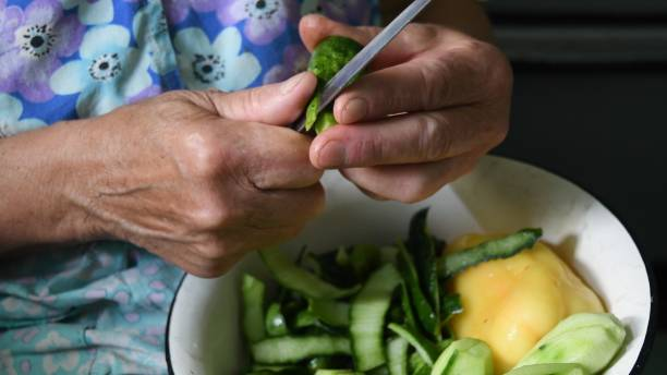 Closeup elder hands peeling cucumber peels with kitchen knife stock photo