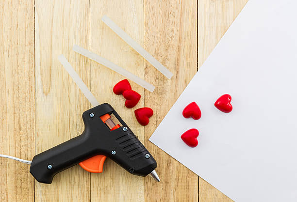 Closeup electric hot glue gun. Closeup electric hot glue gun apply the glue to making postcard with red heart. affix stock pictures, royalty-free photos & images