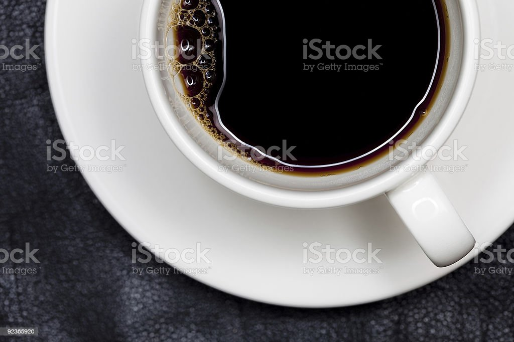 closeup espresso coffee in white cup directly above, black leath royalty-free stock photo