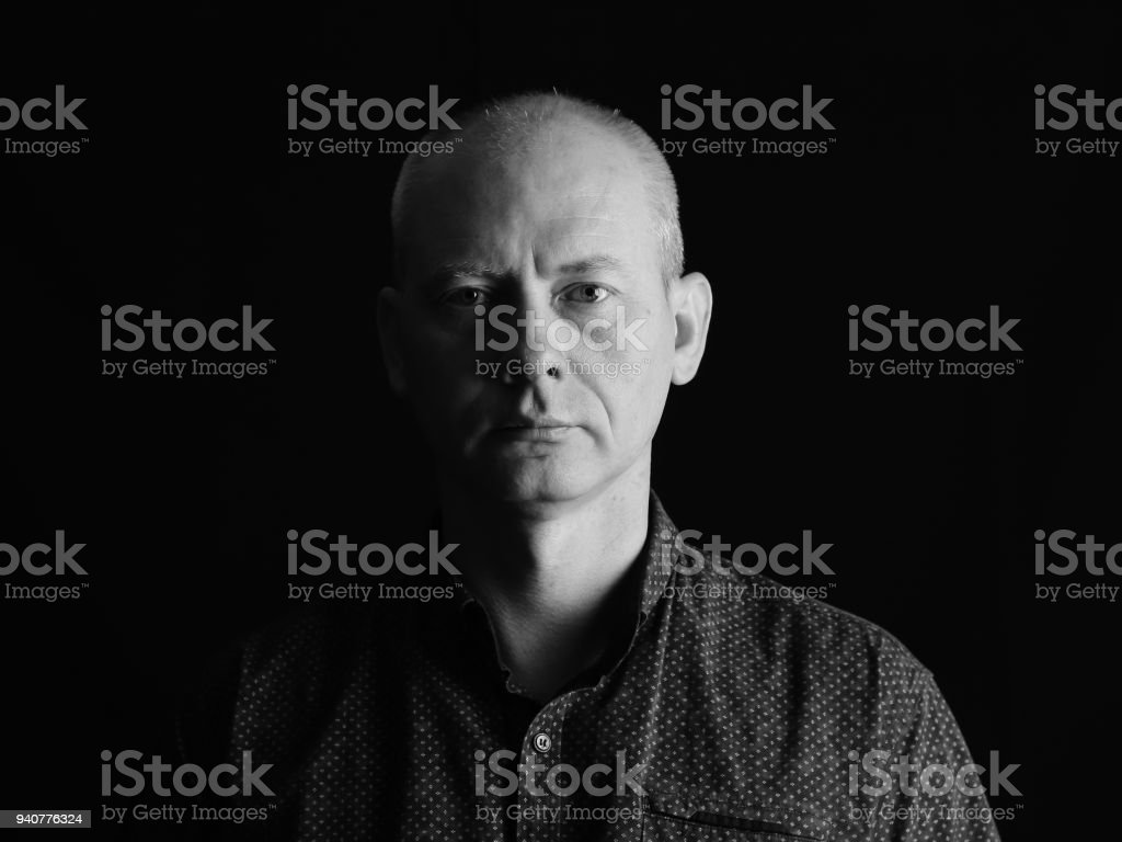 Close-up face of serious man on dark background. stock photo