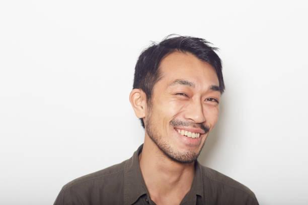 ひげ笑顔で若い男の顔をクローズ アップ - スタジオ 日本人 ストックフォトと画像