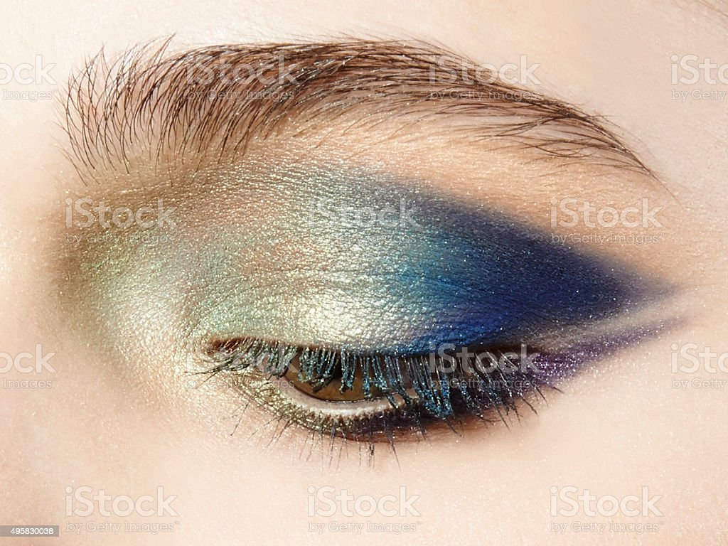 closeup face with closed eye with blue green gold eyeshadow stock photo